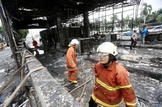Petugas usai memadamkan api yang membakar Gerbang Tol Pejompongan, Jakarta