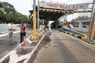 Petugas kepolisian memberikan police line di area kebarakaran Gerbang Tol Pejompongan, Jakarta