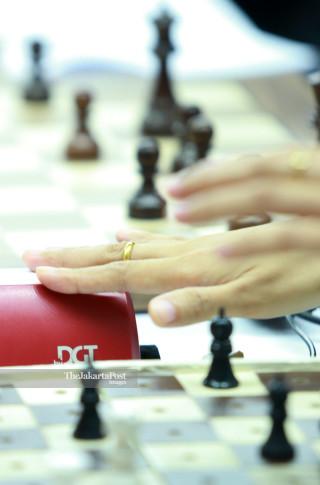 Seorang atlit catur menekan alat pengukur waktu saat bertanding di babak penyisihan catur cepat  ke lima di ajang Asian Para Games 2018, di Jakarta, Jumat (12/10/2018). INAPGOC/Setiyo Sc