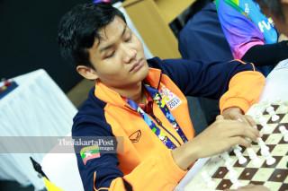 Atlit catur Myanmar San Myo mengangkat  bidak catur  saat bertanding di babak penyisihan catur cepat  ke lima di ajang Asian Para Games 2018, di Jakarta, Jumat (12/10/2018). INAPGOC/Setiyo Sc