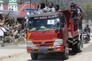 Pekerja bangunan menggunakan kendaraan milik BNPB saat melintas di Jalan Diponegoro Palu Sulawesi Tengah