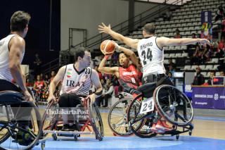 Pemain basket kursi roda Iran berusaha menghalangi operan bola pemain Indonesia