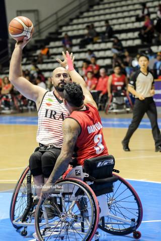 Pemain basket kursi roda Indonesia menghalangi lemparan pemain basket kursi roda Iran.