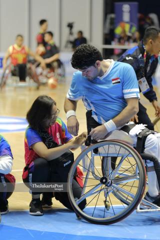 Relawan membantu atlet memasang nomor di Basket Hall GBK.