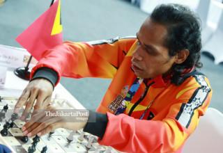 Atlit catur Timor Leste Martins Do Rego mengangkat  bidak catur  saat bertanding di babak penyisihan catur cepat  ke lima di ajang Asian Para Games 2018, di Jakarta, Jumat (12/10/2018). INAPGOC/Setiyo Sc
