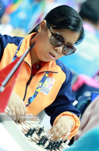 Atlit catur Myanmar Htwe Ohnmar  mengangkat  bidak catur  saat bertanding di babak penyisihan catur cepat  ke lima di ajang Asian Para Games 2018, di Jakarta, Jumat (12/10/2018). INAPGOC/Setiyo Sc