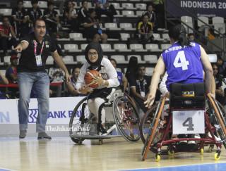 Pebasket kursi roda putri Afganistan Bayat Nilofar (kedua kiri) berusaha melewati hadangan pebasket kursi roda Thailand.