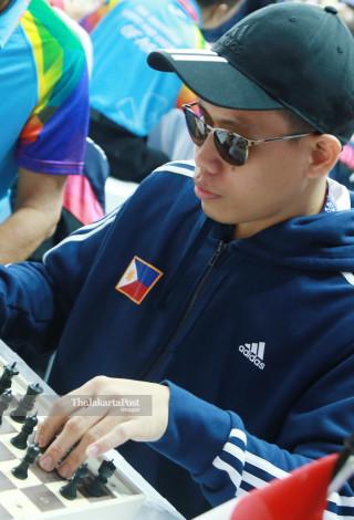 Atlit catur Filiphina Francis Ching mengangkat  bidak catur  saat bertanding di babak penyisihan catur cepat  ke lima di ajang Asian Para Games 2018, di Jakarta, Jumat (12/10/2018). INAPGOC/Setiyo Sc