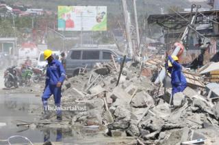Petugas PLN mengganti tiang listrik yang roboh akibat gempa dan tsunami di depan pusat perbelanjaan Palu Grand Mall Sulawesi Tengah
