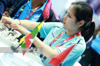 Atlit catur Vietnam Thi Le Xuan Dao mengangkat  bidak catur  saat bertanding di babak penyisihan catur cepat  ke lima di ajang Asian Para Games 2018, di Jakarta, Jumat (12/10/2018). INAPGOC/Setiyo Sc