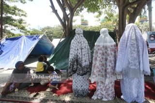 Warga melaksanakan sholat di posko pengungsian di lapangan Masjid Agung Darussalam Palu Sulawesi Tengah