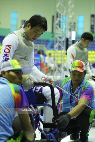 Atlit Anggar Kursi Roda Koorea Selatan Kim Sung Hwan melakukan persiapan dibantu oleh Volunteer dalam pertandingan Wheel Chair Fencing Asian Para Games 2018