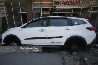 Kendaraan tanpa roda yang menjadi korban penjarahan di depan pusat perbelanjaan Palu Grand Mall, Sulawesi Tengah