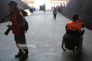 relawan membantu pewarta foto yang berkursi roda